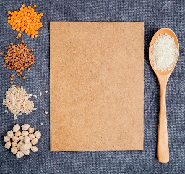 Vista superior de granos de cereales y semillas montones garbanzos arroz alforfón y lentejas rojas con hoja de papel marrón y una cuchara de madera sobre fondo gris Foto gratis