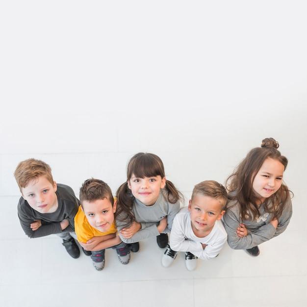 Vista superior grupo de niños posando juntos Foto gratis