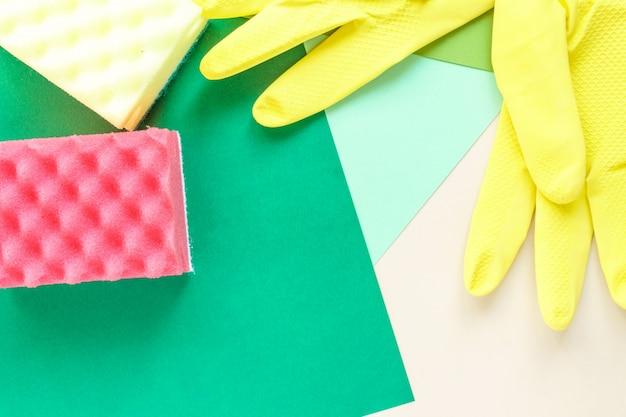 Vista superior de guantes de goma amarilla y dos esponjas sobre fondo brillante multicolor con espacio de copia Foto Premium