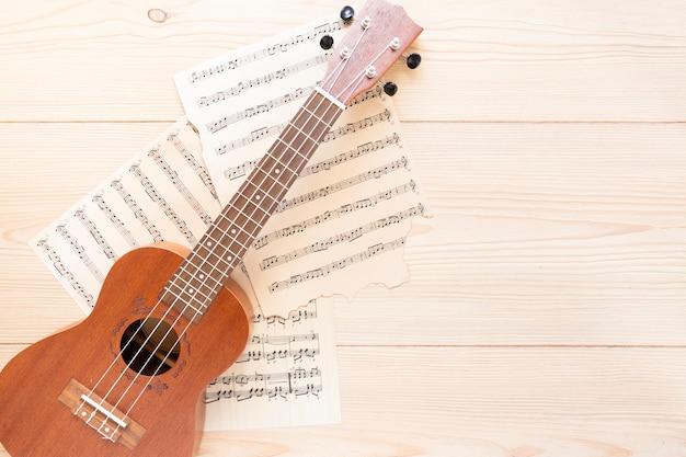 Vista superior guitarra acústica con fondo de madera Foto gratis