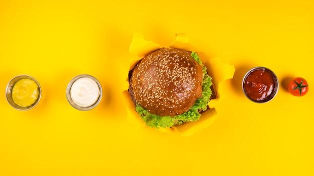 Vista superior hamburguesa clásica con varias salsas Foto gratis