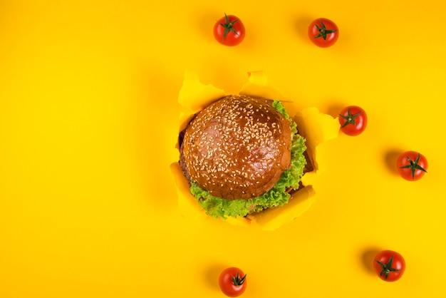 Vista superior hamburguesa de ternera rodeada de tomates cherry Foto gratis