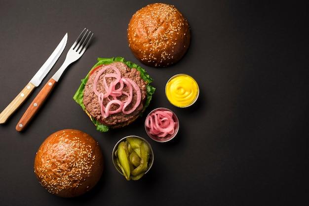 Vista superior hamburguesa de ternera con salsas y cubiertos Foto gratis