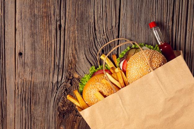 Vista superior de hamburguesas con papas fritas en una bolsa. Foto gratis