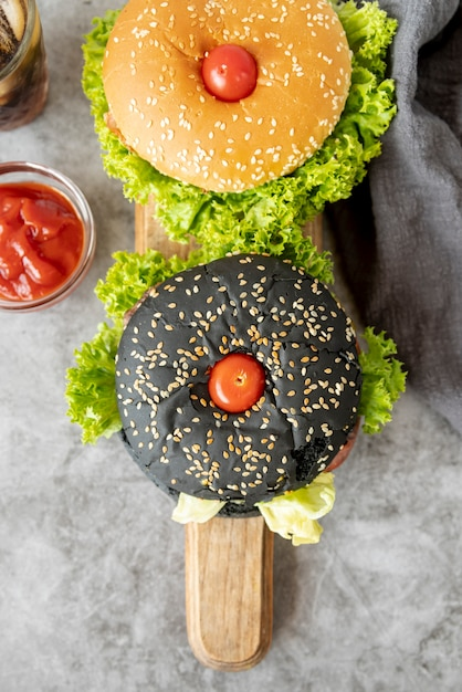 Vista superior de hamburguesas en tabla de cortar Foto gratis