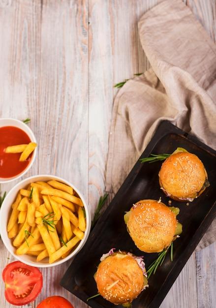 Vista superior hamburguesas de ternera con papas fritas y salsa Foto gratis