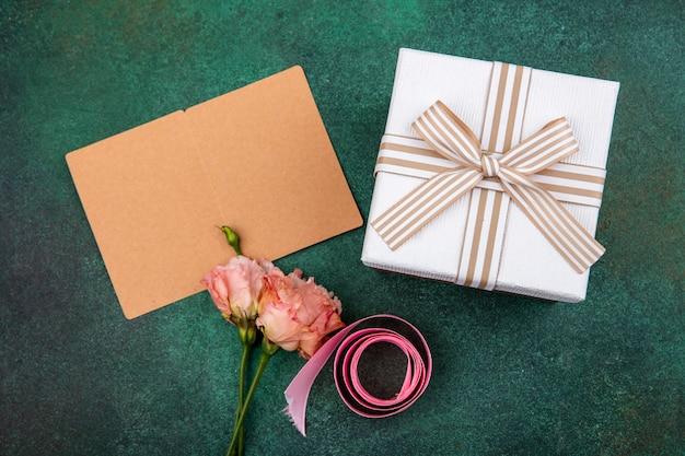 Vista superior de hermosas flores rosadas con cinta rosa con caja de regalo en gre con espacio de copia Foto gratis