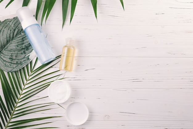 Vista superior hojas tropicales con herramientas de belleza y cosméticos Foto gratis