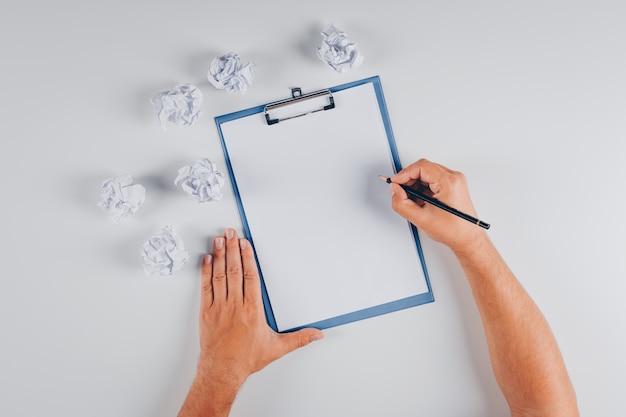 Vista superior hombre escribiendo en portapapeles con papeles arrugados en blanco Foto gratis