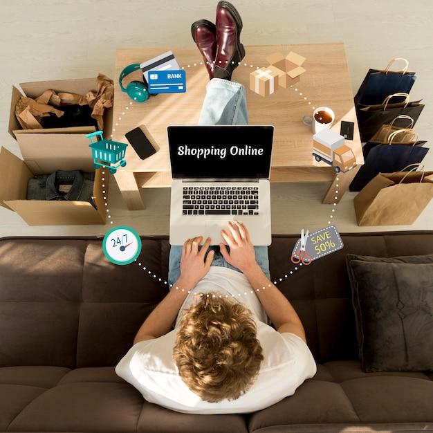 Vista superior del hombre haciendo compras en línea en su computadora portátil Foto gratis