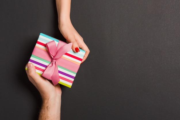 Vista superior de un hombre y una mujer sosteniendo una caja de regalo en colores de fondo Foto Premium