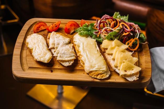 Vista superior, un hombre sostiene una bandeja con tostadas de queso con rodajas de tomate y ensalada de verduras Foto gratis