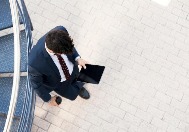 Vista superior del hombre en traje con tableta Foto gratis