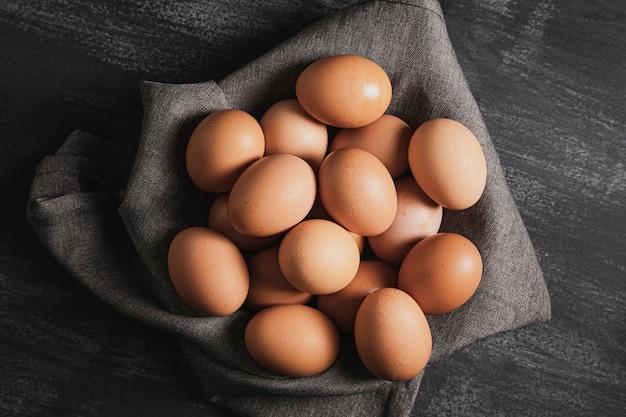 Vista superior huevos sobre tela gris Foto gratis