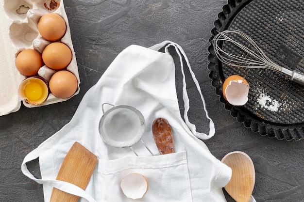 Vista superior de huevos y utensilios de cocina. Foto gratis