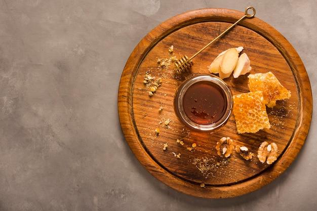 Vista superior jarra de miel con comida y cuchara de miel Foto gratis