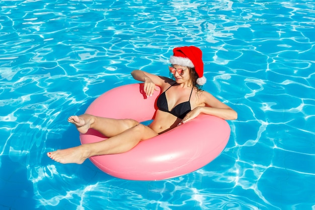 Vista superior de la joven hembra en santa claus hat nadar con círculo rosa en la piscina Foto Premium
