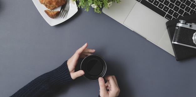 Vista superior de la joven mujer sosteniendo la taza de café en el espacio de trabajo de invierno con material de oficina Foto Premium