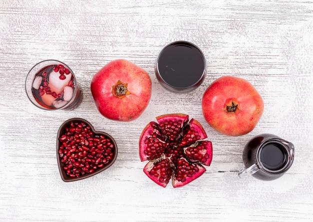 Vista superior de jugo de granada y semillas de granada en placa en forma de corazón sobre la mesa de madera blanca Foto gratis