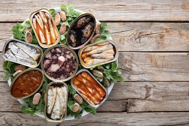 Vista superior de latas de mariscos en un plato con espacio de copia Foto gratis