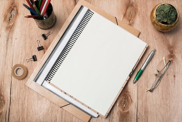 Vista superior del libro espiral en blanco; los anteojos; planta y suministros de oficina en mesa. Foto gratis