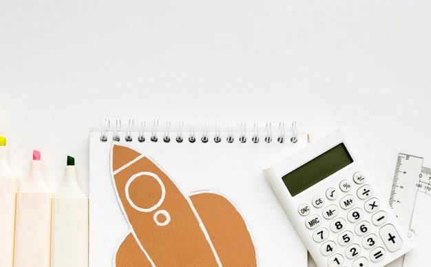 Vista superior de lo esencial para el regreso a la escuela con un cuaderno y una calculadora Foto gratis