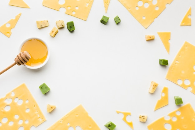 Vista superior de lonchas de queso emmental con marco de miel Foto gratis