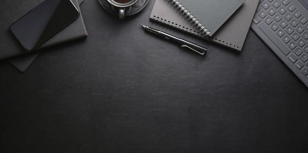 Vista superior del lugar de trabajo oscuro y elegante con teléfonos inteligentes y suministros de oficina Foto Premium