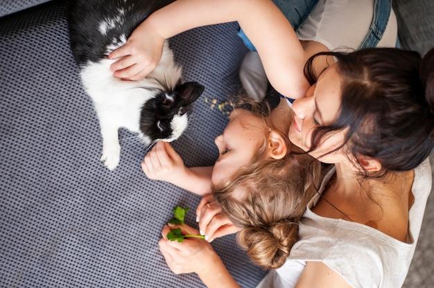 Vista superior madre y niña acariciando conejo pequeño Foto gratis
