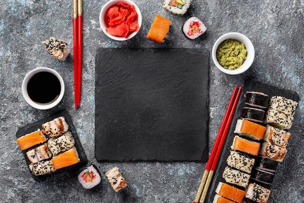 Vista superior maki sushi rolls palillos y salsa de soja con pizarra en blanco Foto gratis