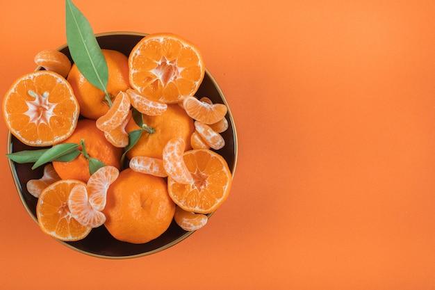 Vista superior de mandarinas en placa con espacio de copia en superficie naranja Foto gratis