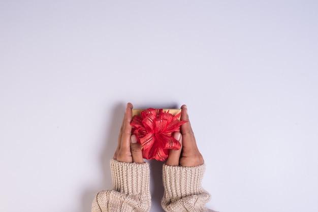 Vista superior de la mano con caja de regalo en el espacio de trabajo Foto gratis