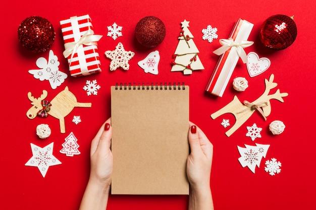 Vista superior de la mano femenina haciendo algunas notas en noteebok sobre fondo colful. decantaciones de año nuevo y juguetes. concepto de tiempo de navidad Foto Premium