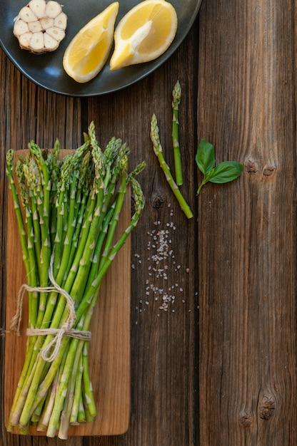 Vista superior del manojo de espárragos verdes frescos con el limón y el ajo en la tabla de madera Foto Premium