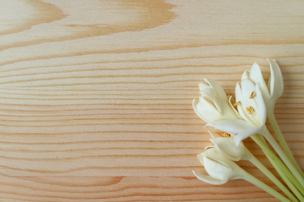 Vista superior de un manojo de flores blancas puras de millingtonia en una mesa de madera de color marrón claro Foto Premium