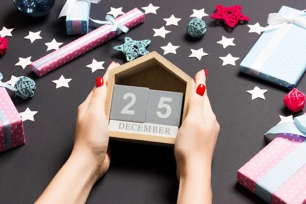 Vista superior manos femeninas con calendario en negro. el veinticinco de diciembre. decoraciones navideñas. tiempo de navidad Foto Premium