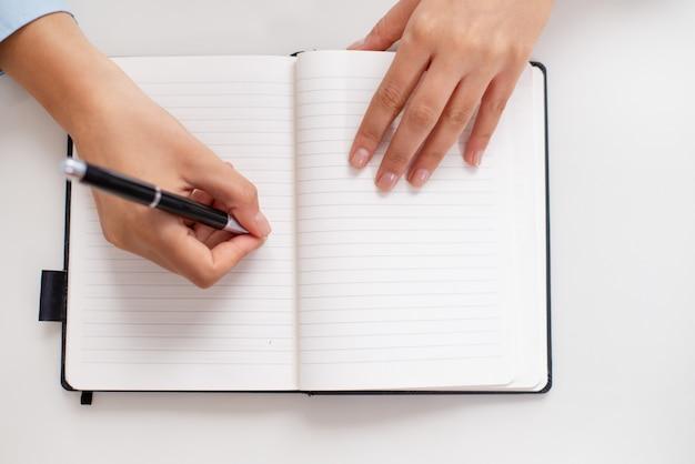 Vista superior de las manos femeninas que escriben en cuaderno en el escritorio Foto gratis