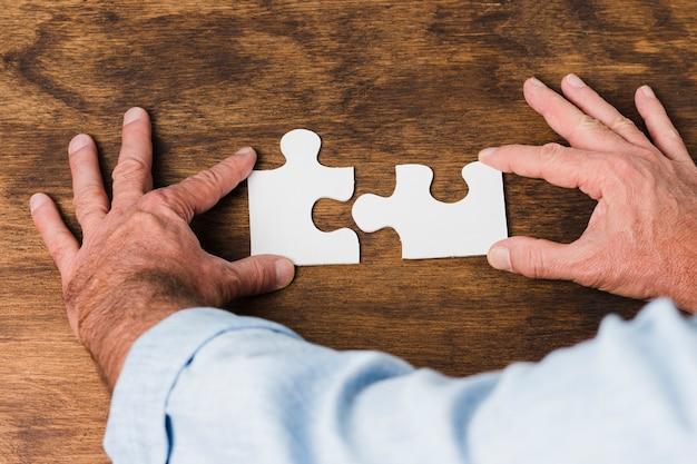 Vista superior manos haciendo puzzle sobre mesa de madera Foto gratis