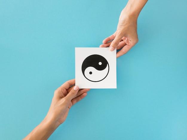 Vista superior de manos intercambiando símbolos ying y yang Foto gratis