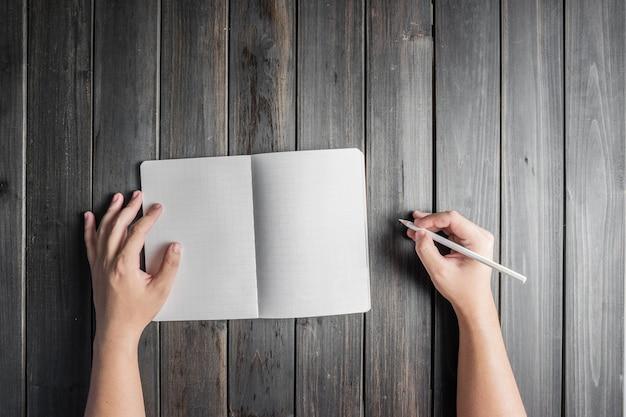 Vista superior de manos con lápiz y un cuaderno abierto Foto gratis