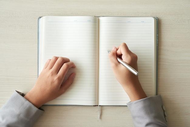 Vista superior de las manos de una persona irreconocible lista para completar el planificador Foto gratis