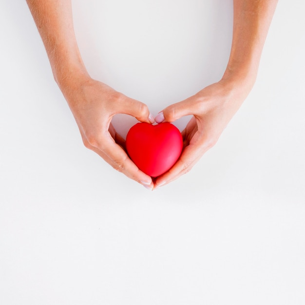 Vista superior de las manos sosteniendo el día mundial del corazón en forma de corazón Foto gratis