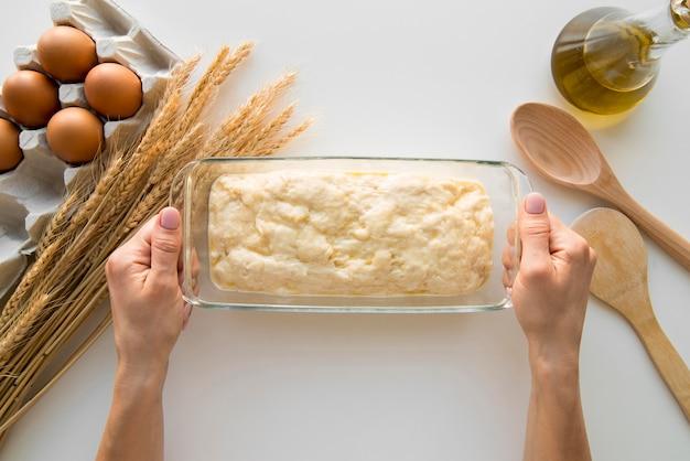 Vista superior manos sosteniendo molde de pastel con masa Foto gratis