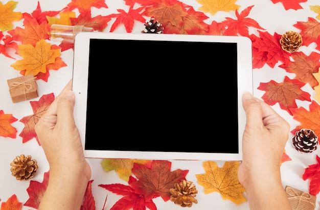 Vista superior manos sostienen tableta en blanco con coloridas hojas de otoño de arce y cajas de regalo, concepto de otoño Foto Premium