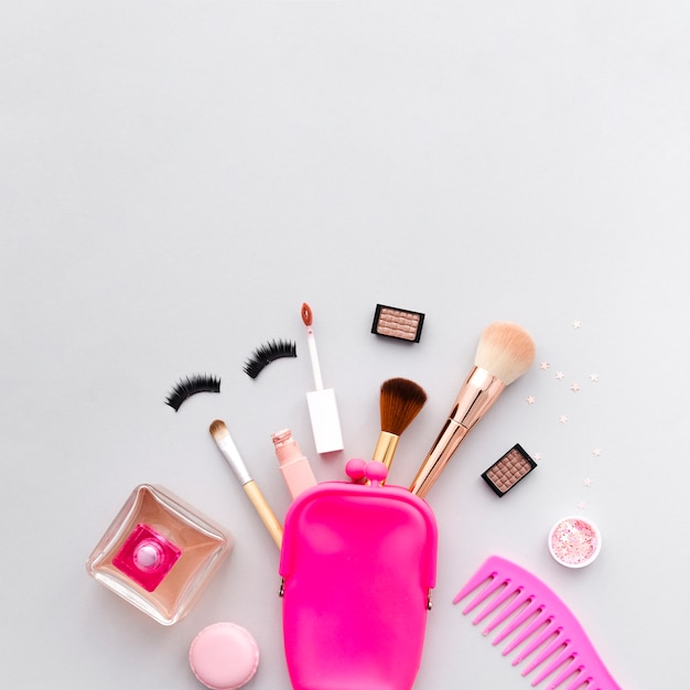 Vista superior maquillaje saliendo de neceser Foto gratis