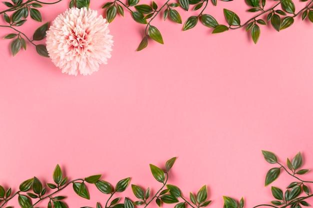 Vista superior del marco de follaje en papel con flor Foto gratis