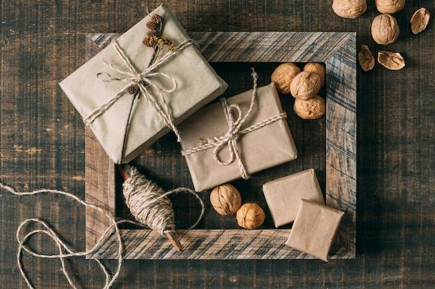 Vista superior marco de madera con regalos y nueces Foto gratis