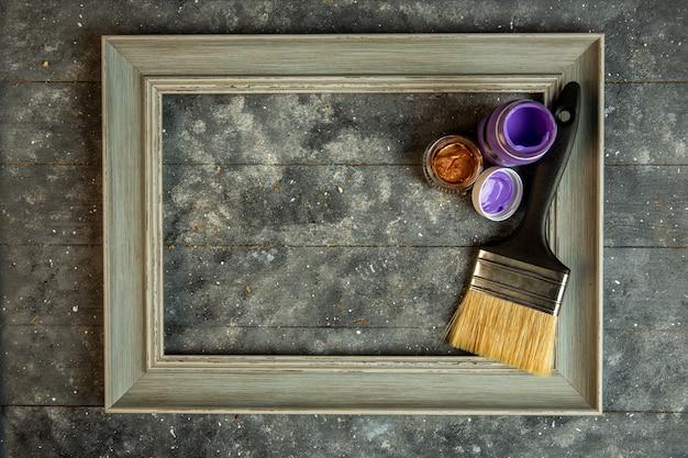 Vista superior del marco de madera vacío con pinturas acrílicas y pincel Foto gratis