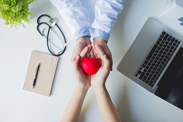 Vista superior . médico y paciente manos sosteniendo corazón rojo sobre mesa blanca Foto Premium