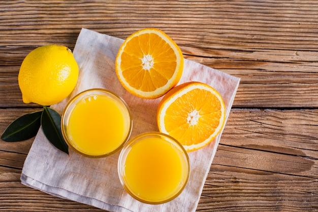 Vista superior medio corte de naranjas y vasos con jugo Foto gratis